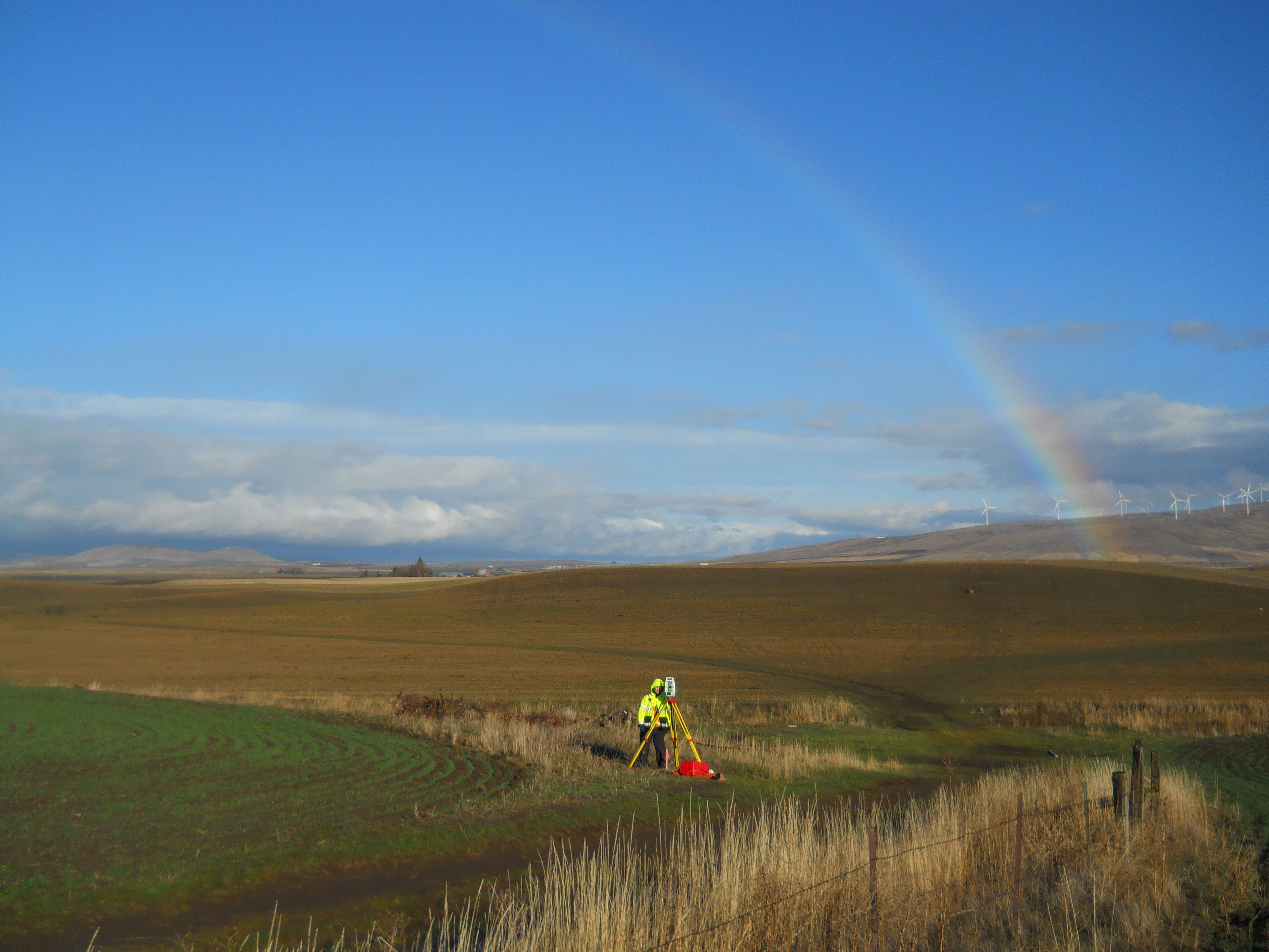 Surveyor in a field with rainbow